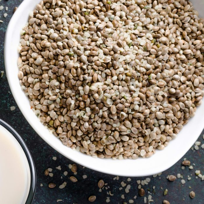 Hemp seed milk in a glass pitcher with hemp seed in a bowl on a dark stone table.