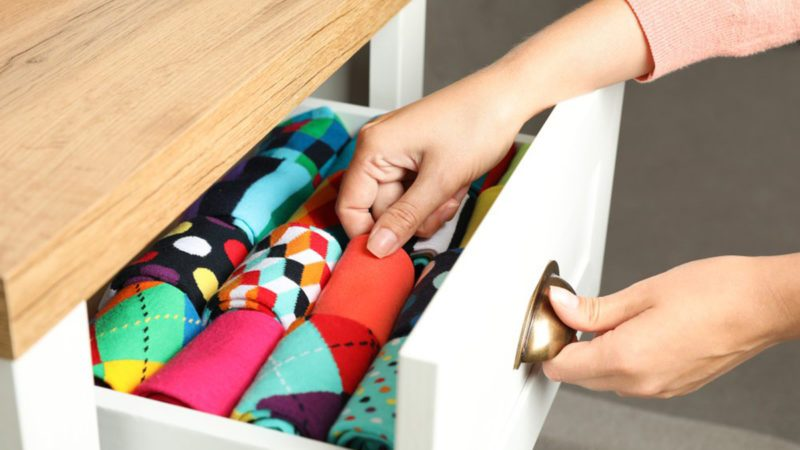 Woman pulling clothes from a drawer