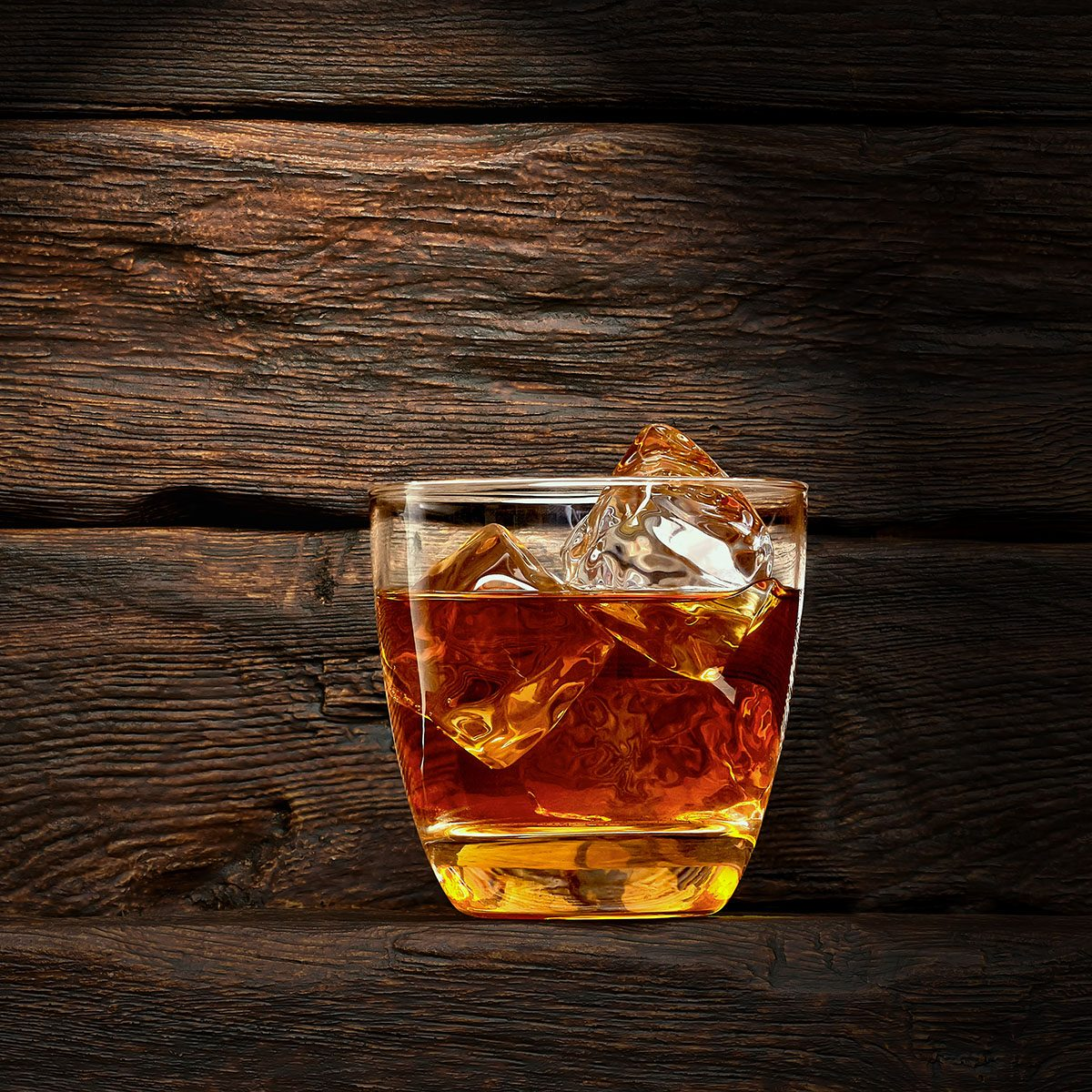 Cola with whiskey on wooden background