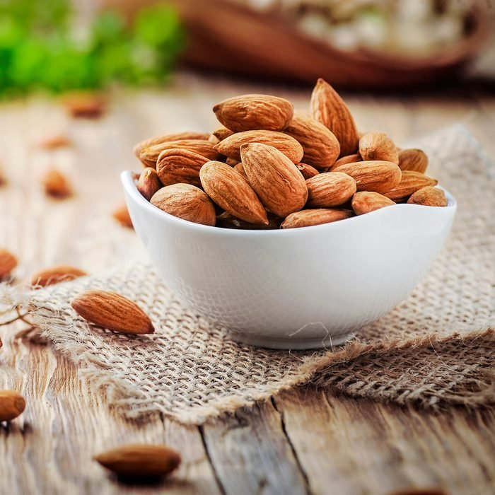 Almonds in white porcelain bowl on wooden table