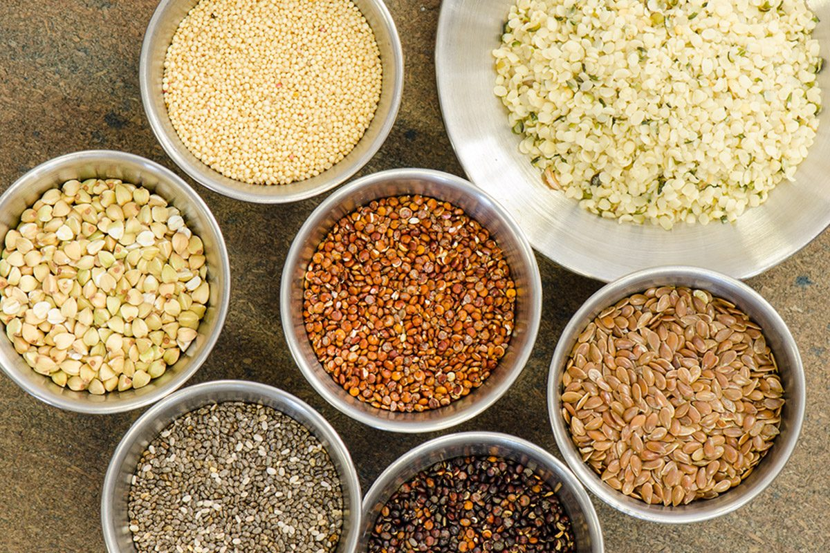 Ancient grains and healthy organic edible seeds in round stainless steel containers.
