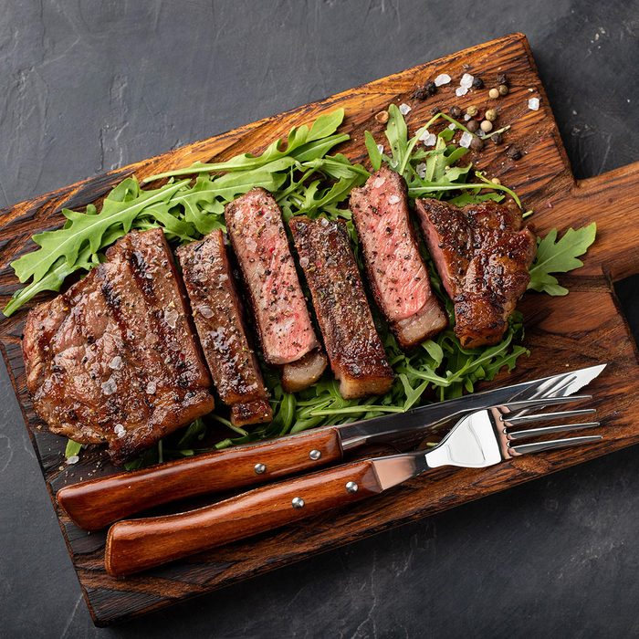 Closeup ready to eat steak new York beef breeds of black Angus with herbs, garlic and butter on a wooden Board. The finished dish for dinner on a dark stone background.
