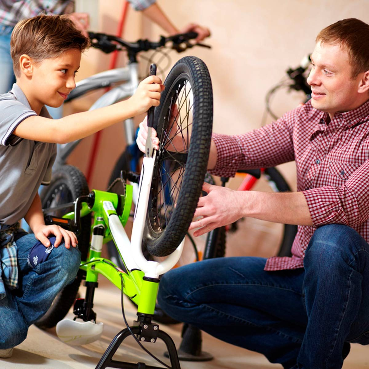 Parent and child working together on an upturned bike