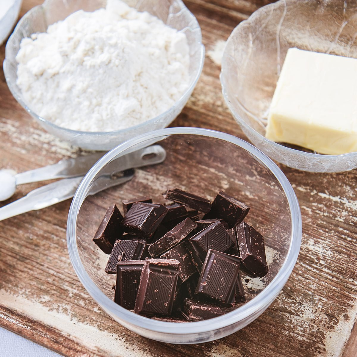 Baking ingredients for chocolate cake muffins or cookies lying ready on wooden kitchen tray.