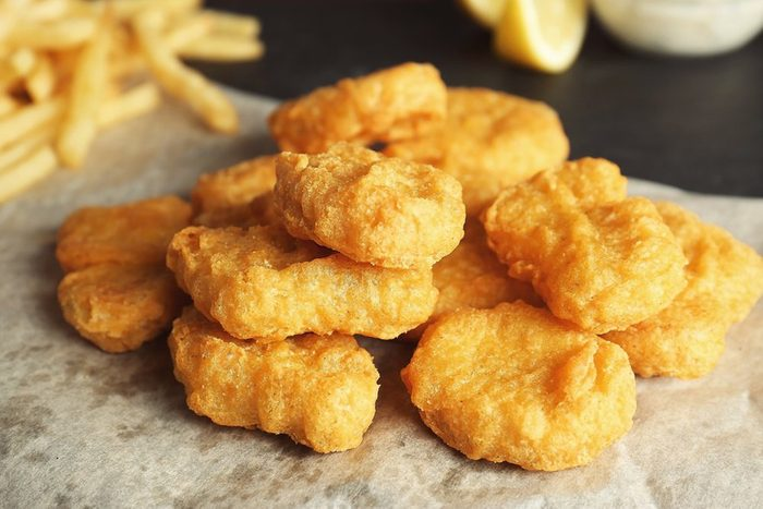 Tasty fried nuggets on paper, closeup