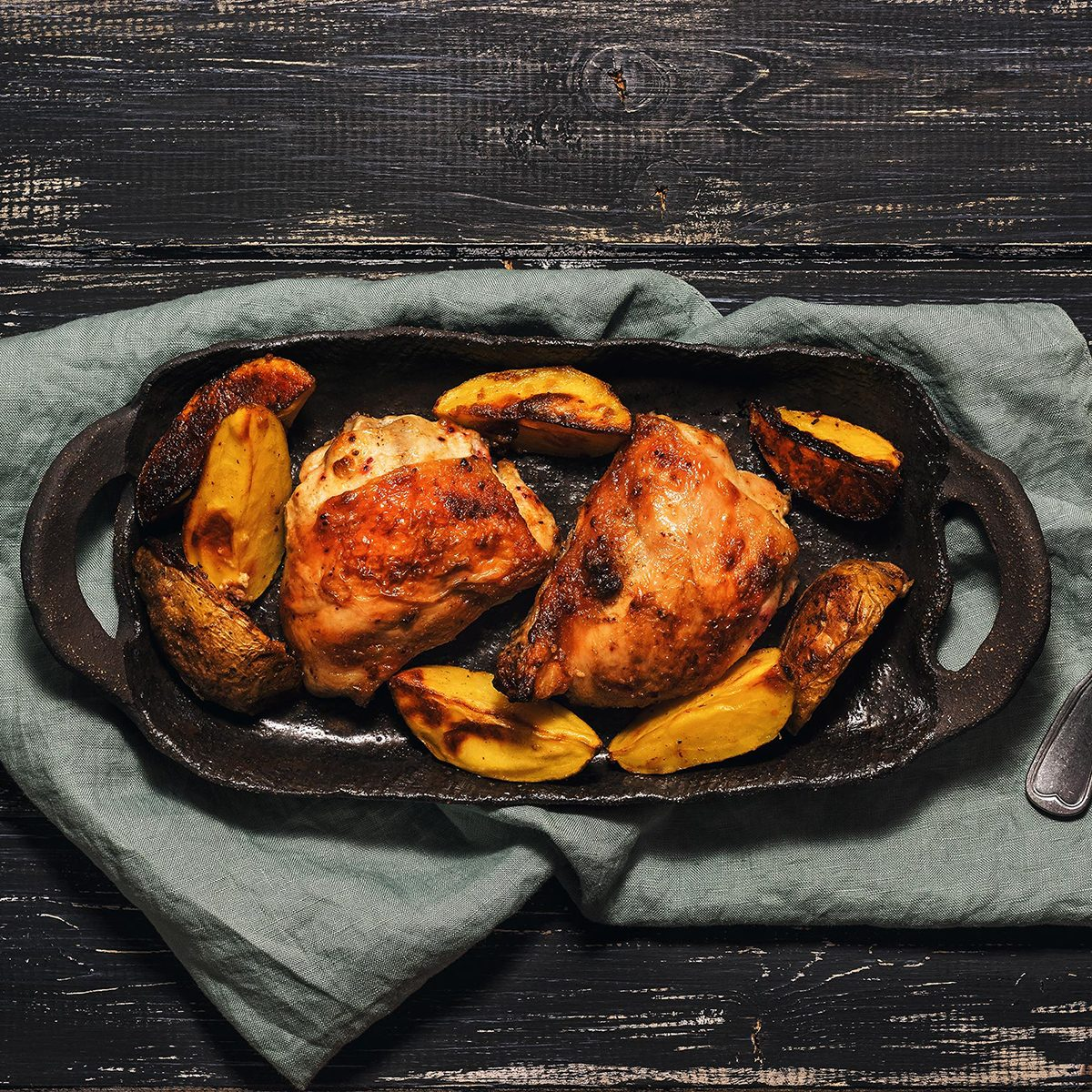 Chicken thigh baked with potatoes on a black dish.
