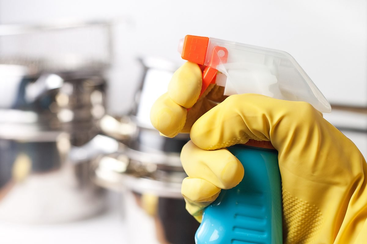 Hand in protective glove holding spray.