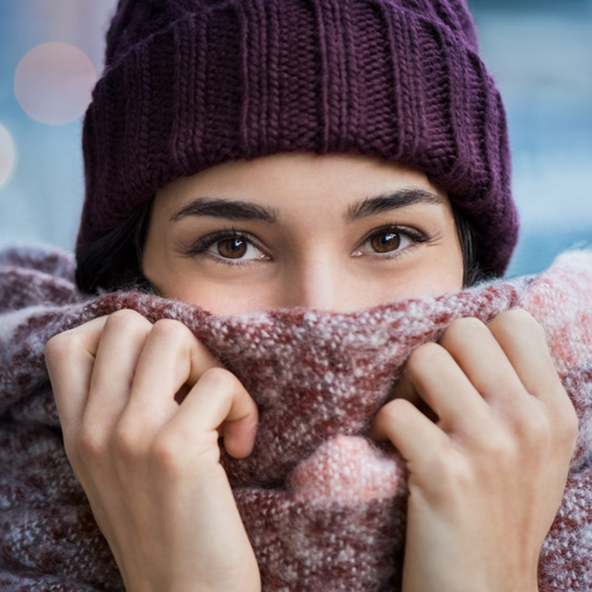 Winter portrait of young beautiful woman covering face with woolen scarf.