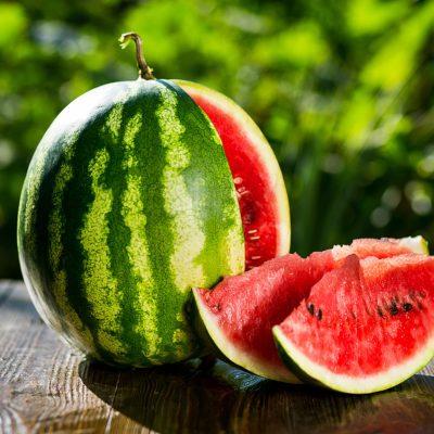 Fresh ripe striped sliced watermelon on wooden background