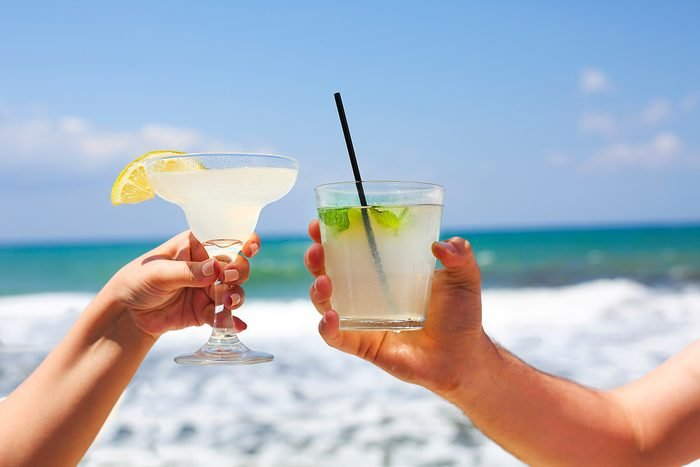 Two cocktail glasses in man and woman hands. Margarita and mojito cocktail