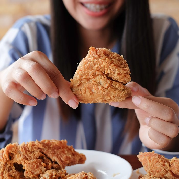close up focus woman hand hold fried chicken for eat