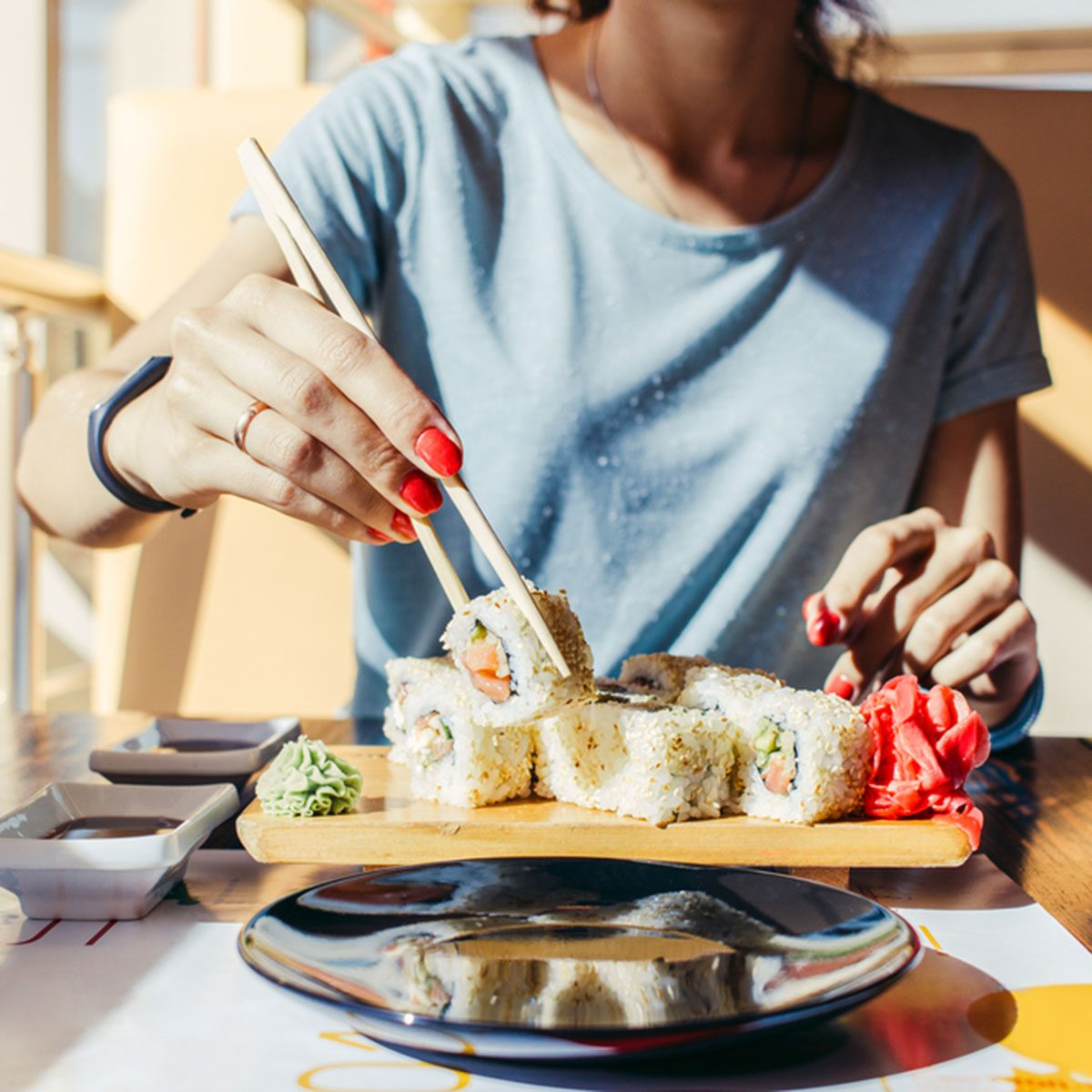 Woman in the blue shirt is eating at a sushi restaurant in summer