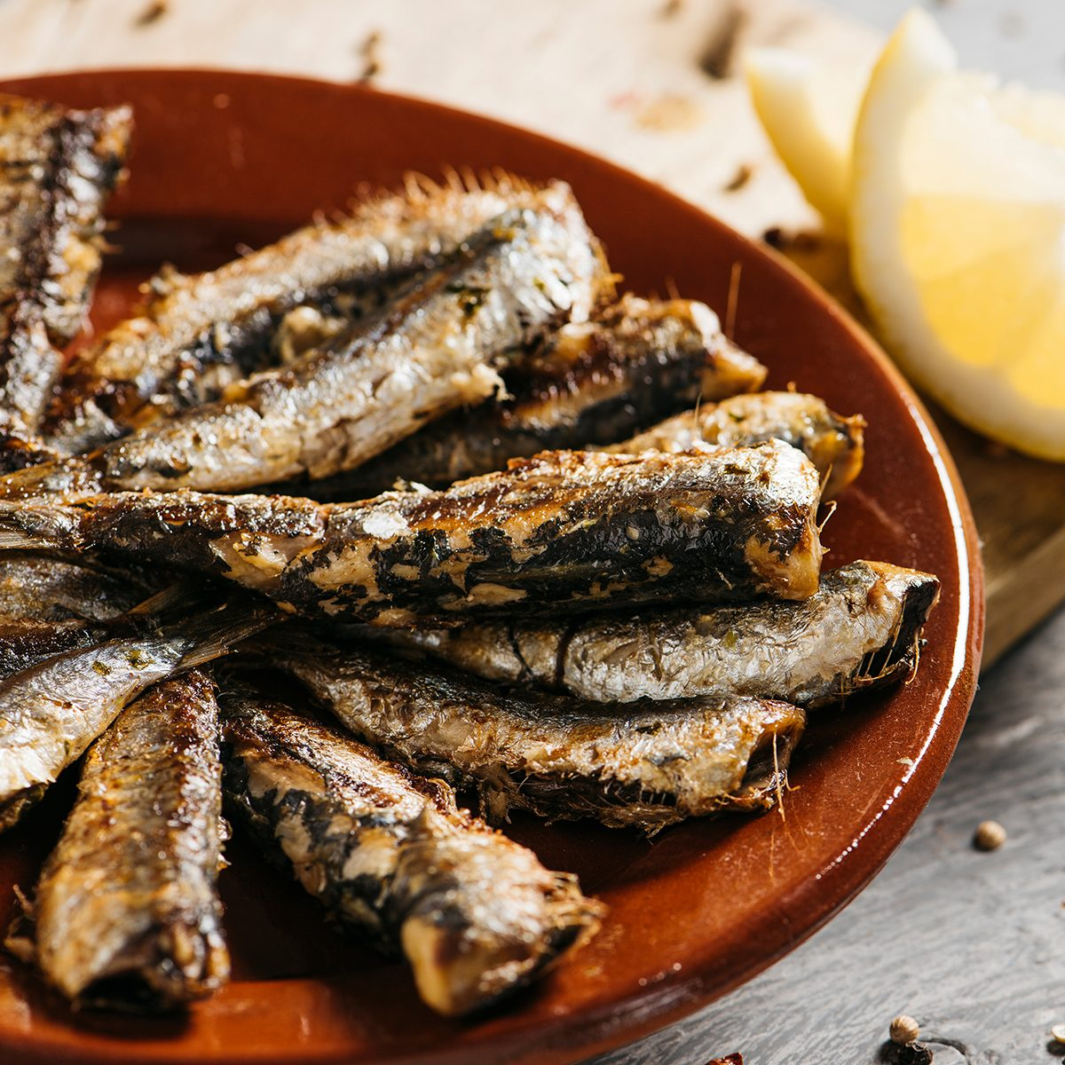 closeup of some spanish grilled sardines in a brown earthenware plate