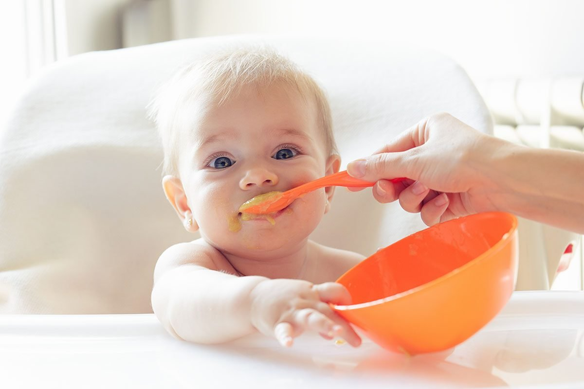 Beautiful baby eating mashed