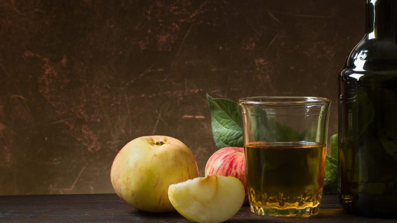Glass of cider with apples and bottle on rustic wooden background