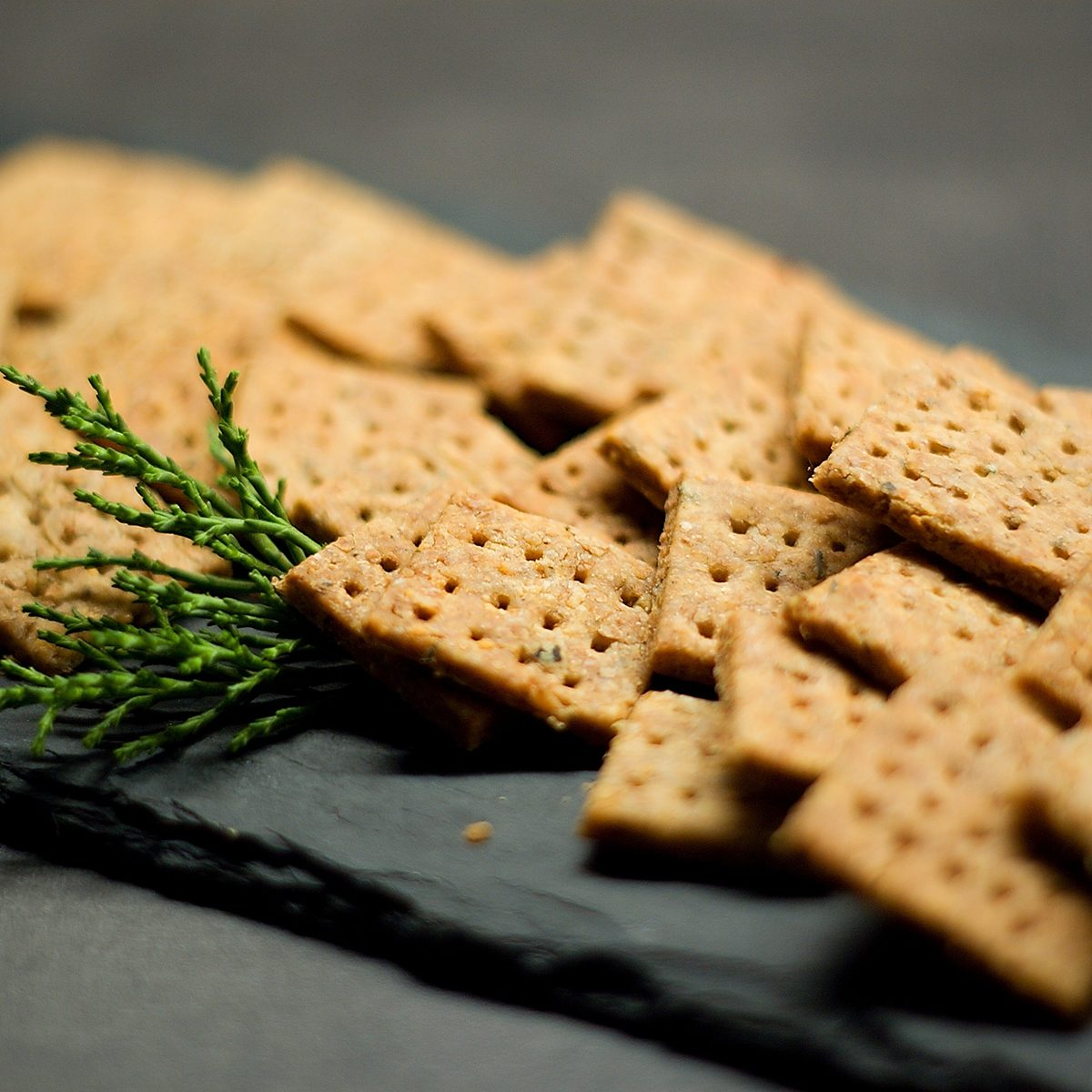 Homemade cheese whole grain squared crackers on slate tray