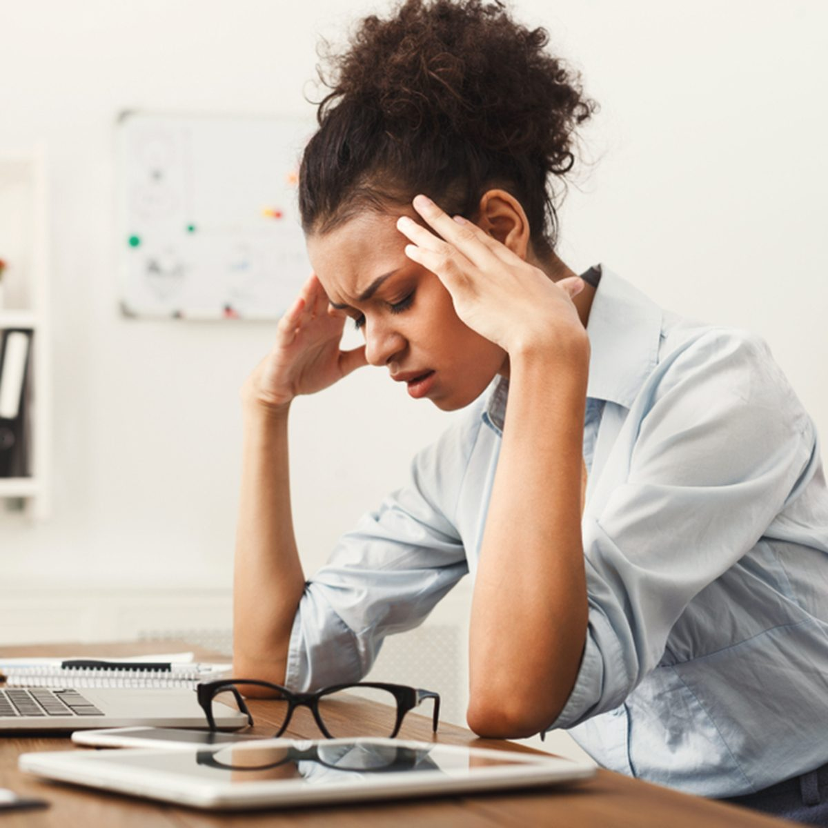 Tired african-american business woman with headache at office