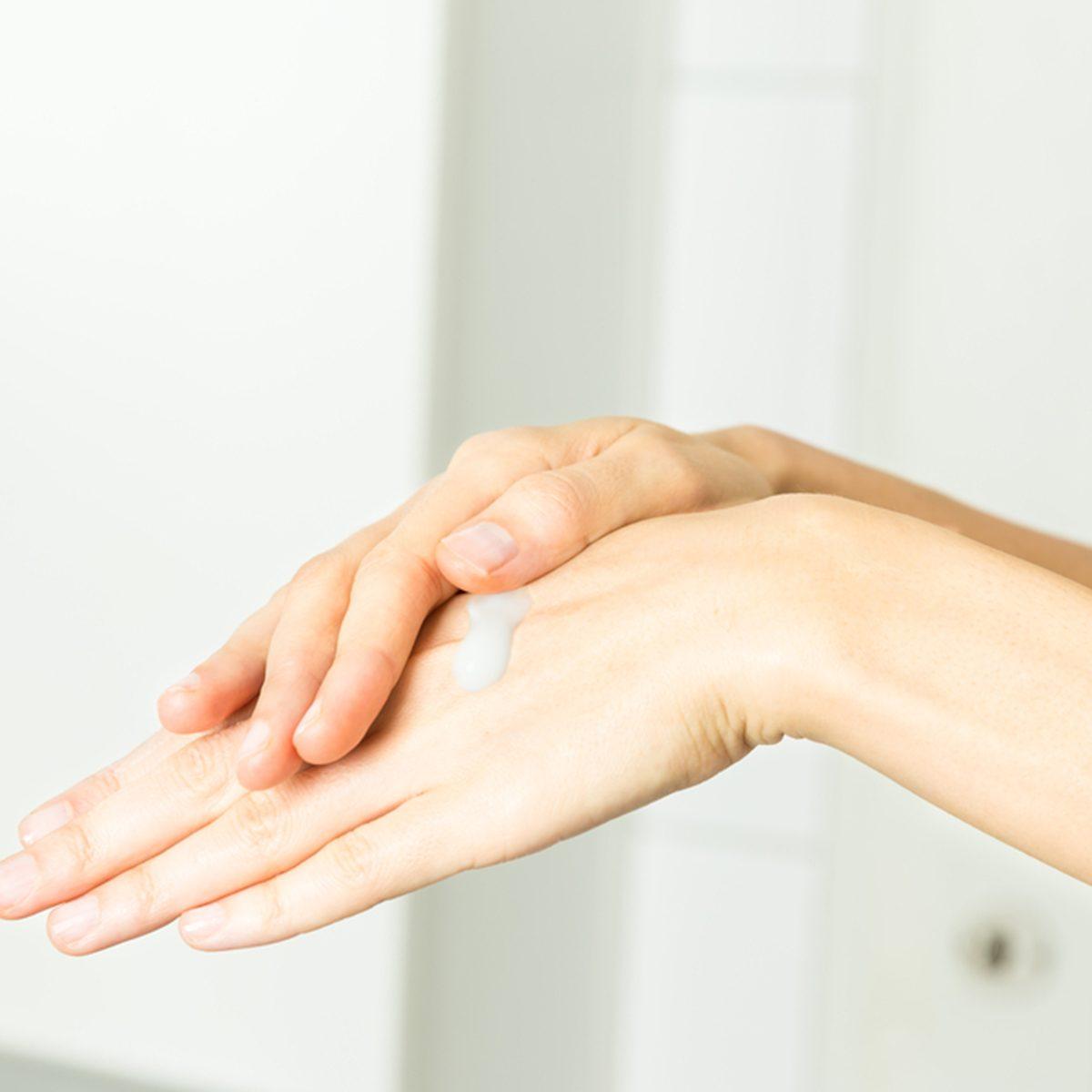 Female hands applying cream
