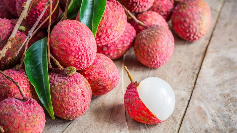 Lychee, Fresh lychee and peeled showing the red skin and white flesh with green leaf on a wooden background