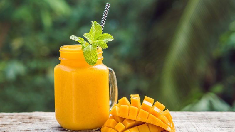 Mango smoothie in a glass Mason jar and mango on a green background.