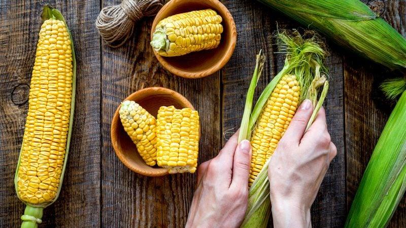 Woman's hands clean corn cob.
