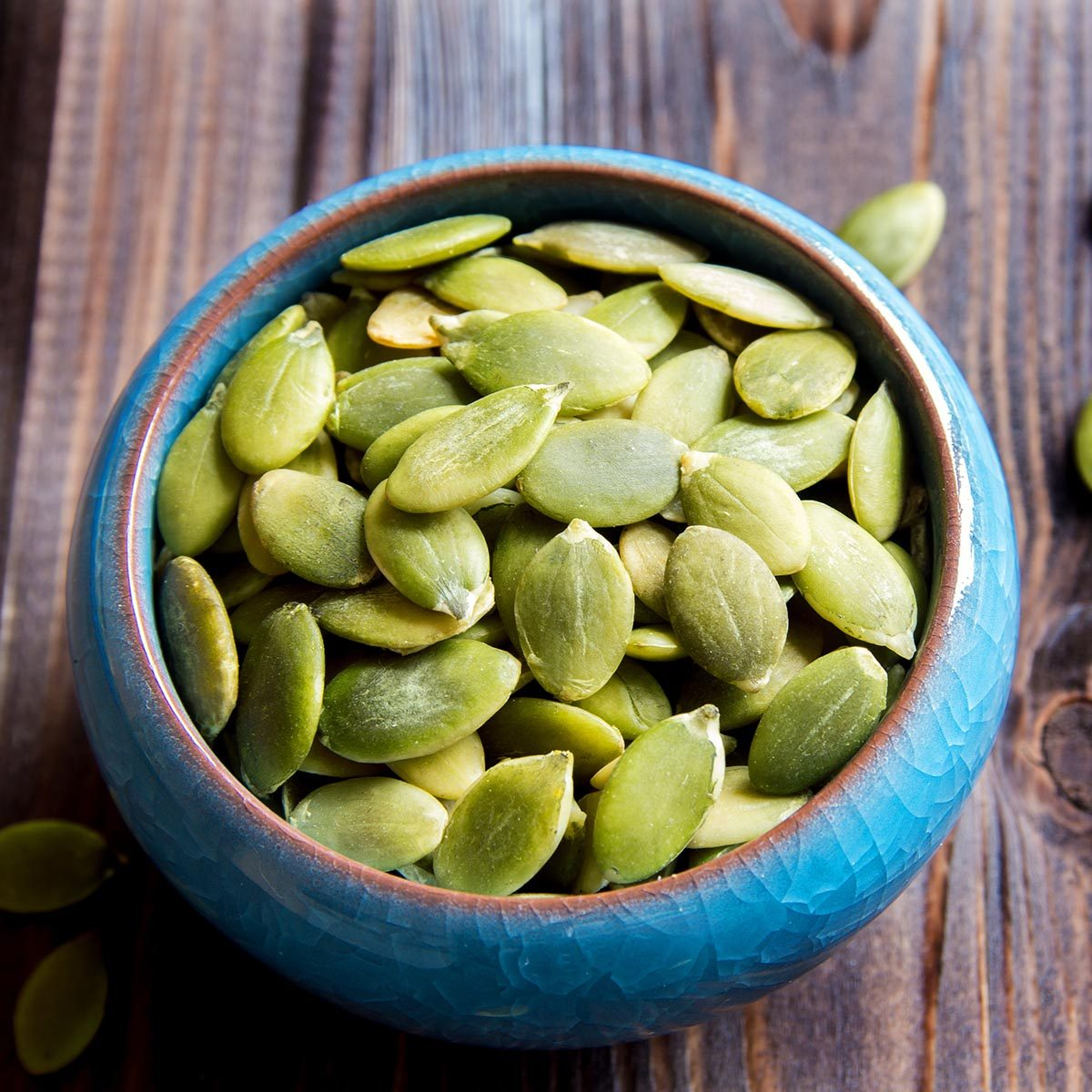 Pumpkin seeds in blue bowl over wooden background close up