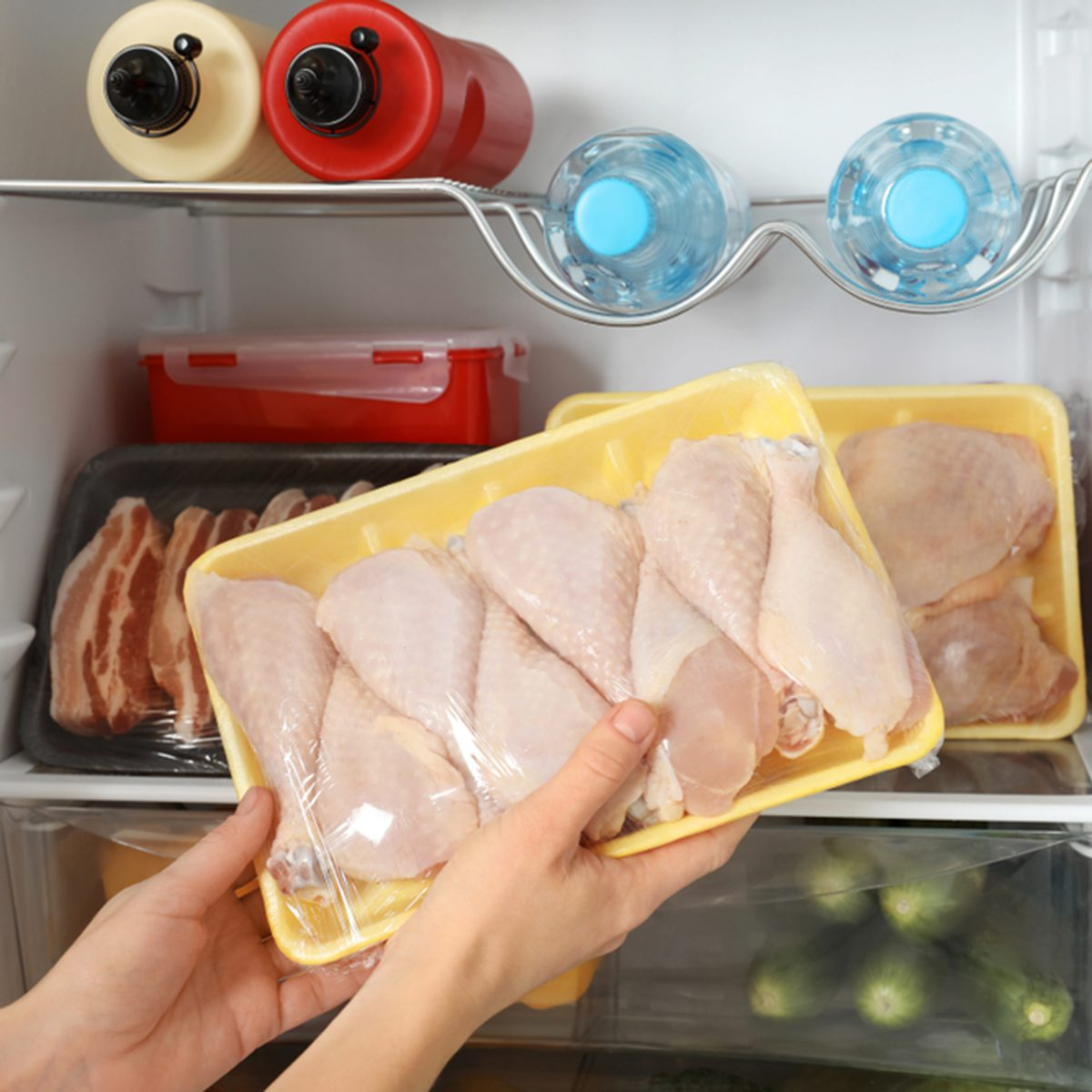 Woman taking raw chicken drumsticks from refrigerator, closeup