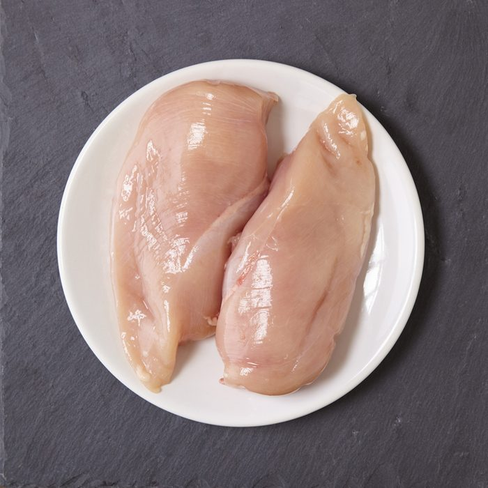 Food and raw meat - uncooked chicken breast fillets on a plate, on a rustic slate counter top background