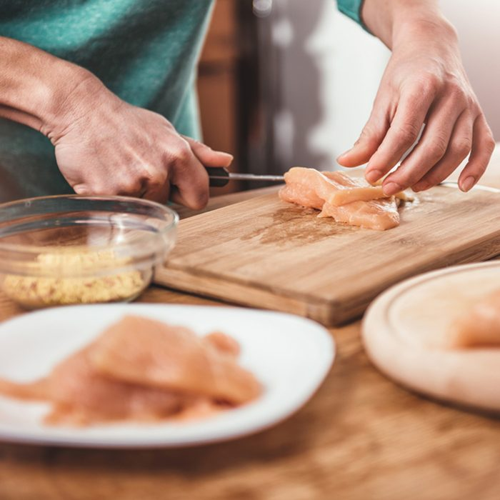 Woman cutting chicken breast on the table