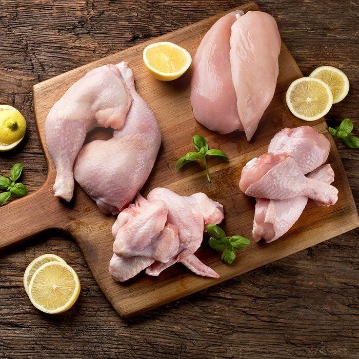 Raw chicken meat on wooden board.