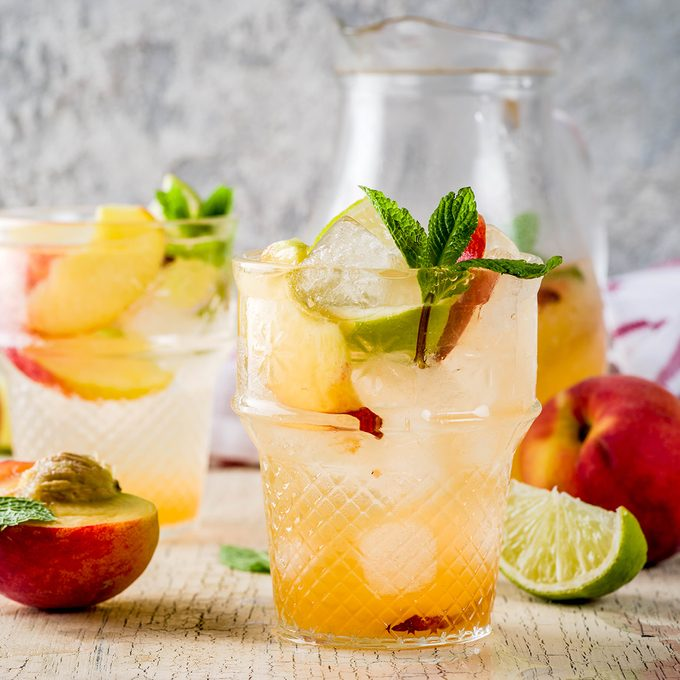 Peach and lime lemonade, mojito cocktail with fresh fruit garnish, om light concrete background copy space selective focus; Shutterstock ID 1139051825; Job (TFH, TOH, RD, BNB, CWM, CM): Taste of Home