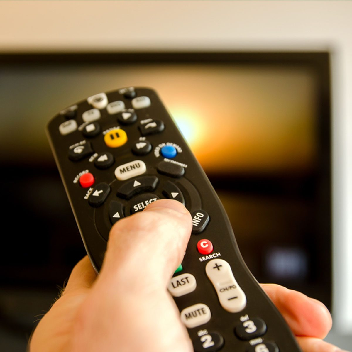 Watching tv and using remote control; Shutterstock ID 137593505