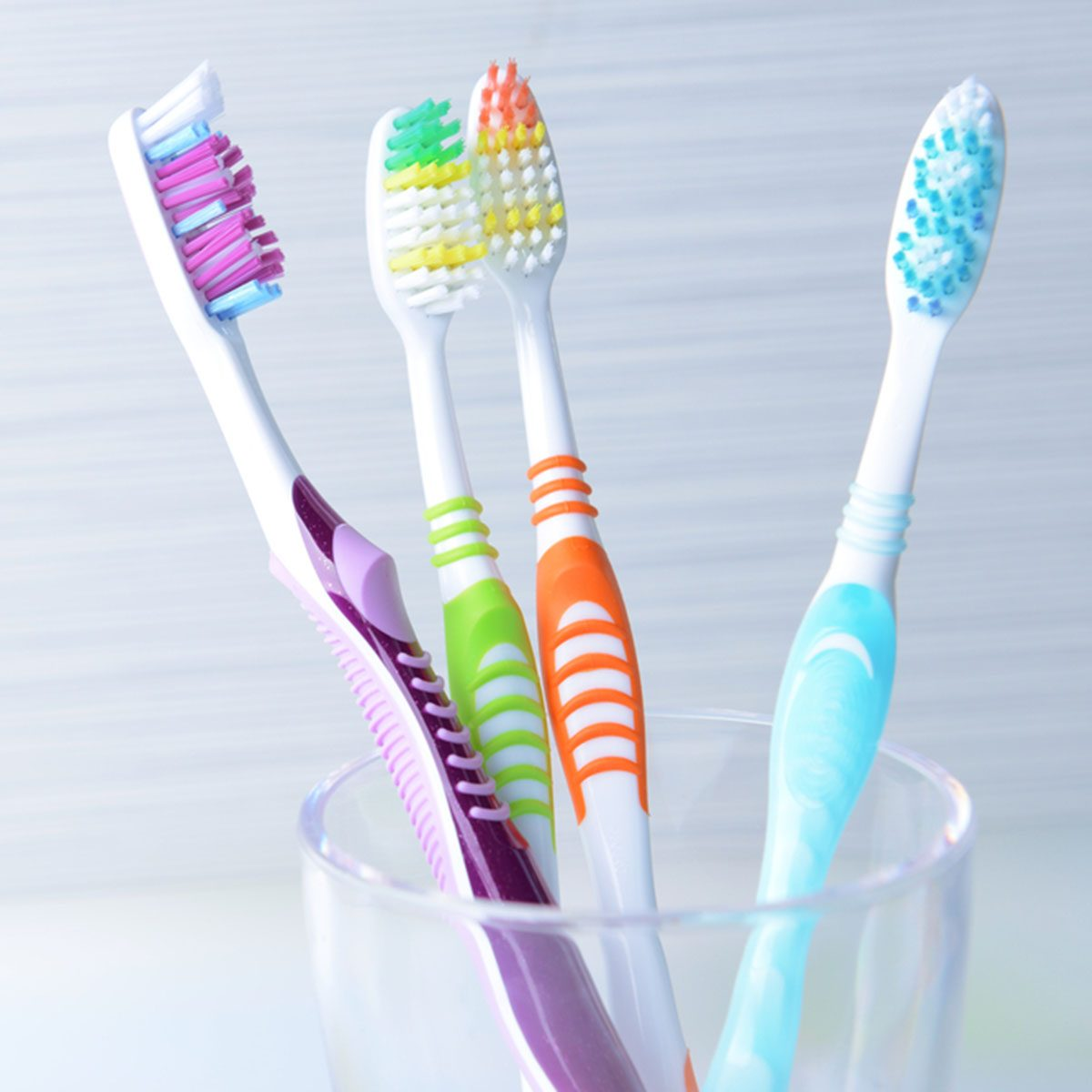Toothbrushes in glass on table on light background; Shutterstock ID 194646521; Job (TFH, TOH, RD, BNB, CWM, CM): Taste of Home