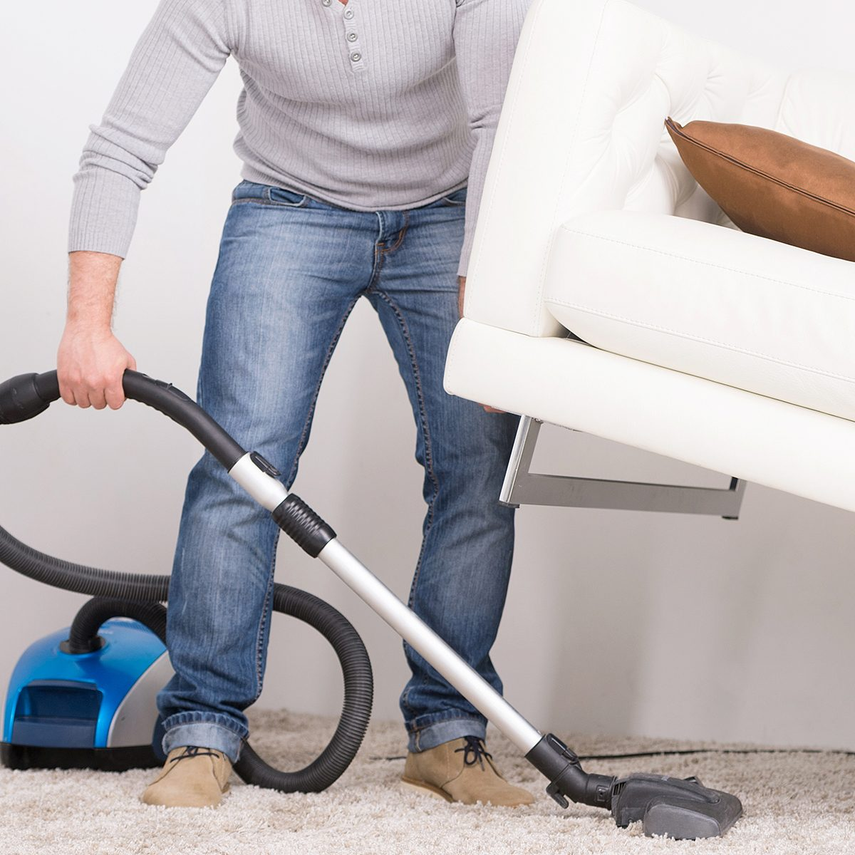 man does house work with vacuum cleaner. Men lifted sofa in living room, vacuum cleaning. ; Shutterstock ID 216002761; Job (TFH, TOH, RD, BNB, CWM, CM): TOH