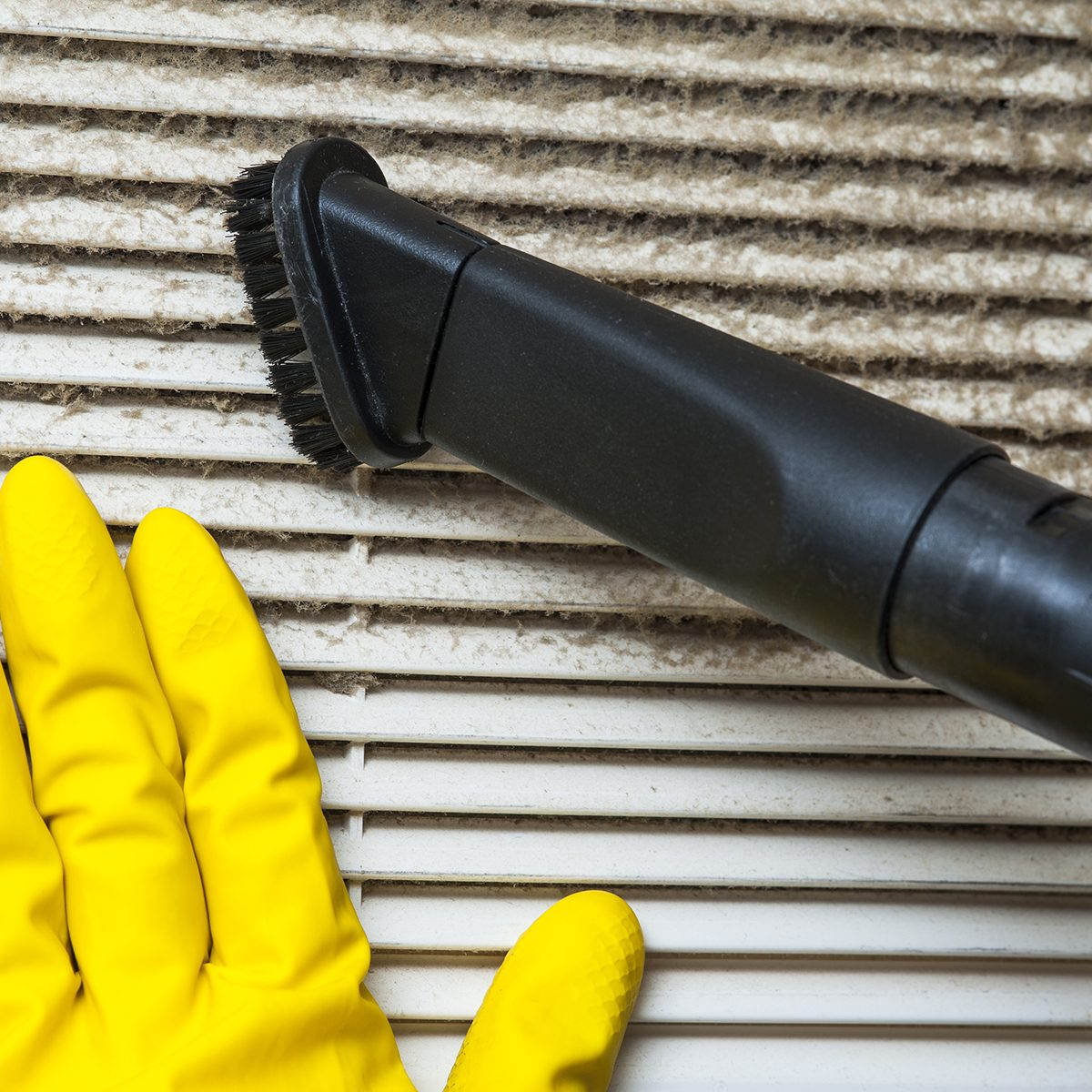 Hand in yellow glove and vacuum cleaner pipe. Ventilation grill cleaning.; Shutterstock ID 389950375; Job (TFH, TOH, RD, BNB, CWM, CM): TOH