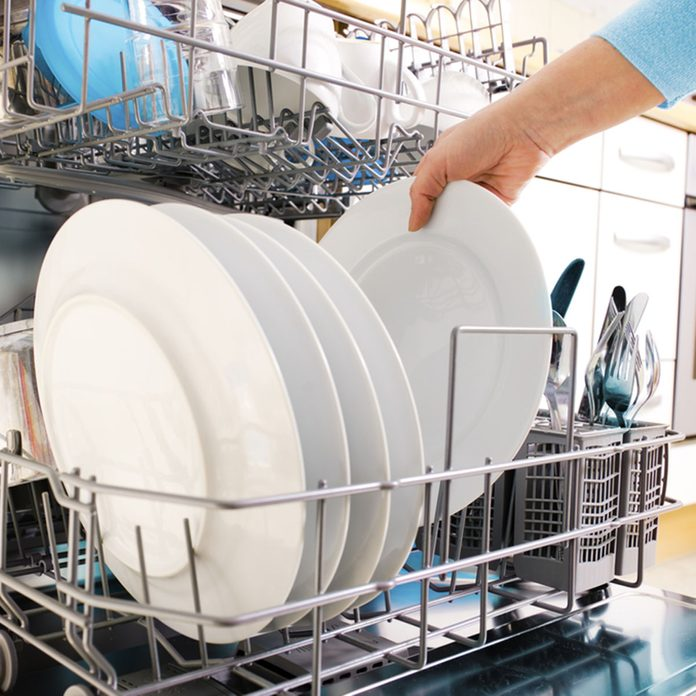close-up of female hands loading dishes to the dishwasher; Shutterstock ID 53629048