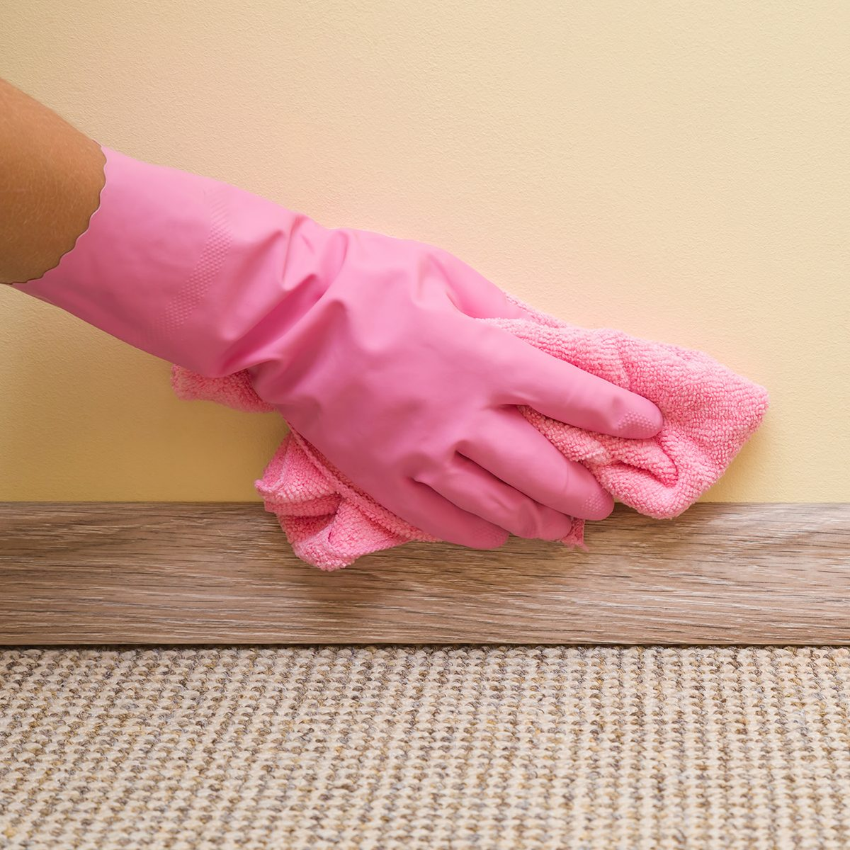 Hand in rubber protective glove with microfiber cloth cleaning baseboard on the floor from dust at the wall. Early spring cleaning or regular clean up. Maid cleans house.; Shutterstock ID 687988345