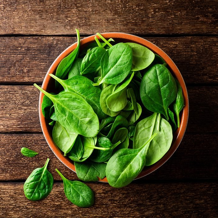 Fresh spinach leaves in bowl on rustic wooden table.