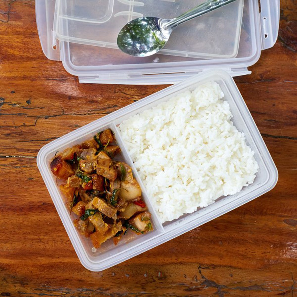 Plastic kitchen containers, one filled with rice and meat