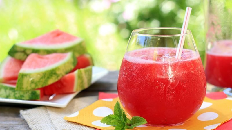 watermelon juice recipe outside in the garden with straws and fresh mint.