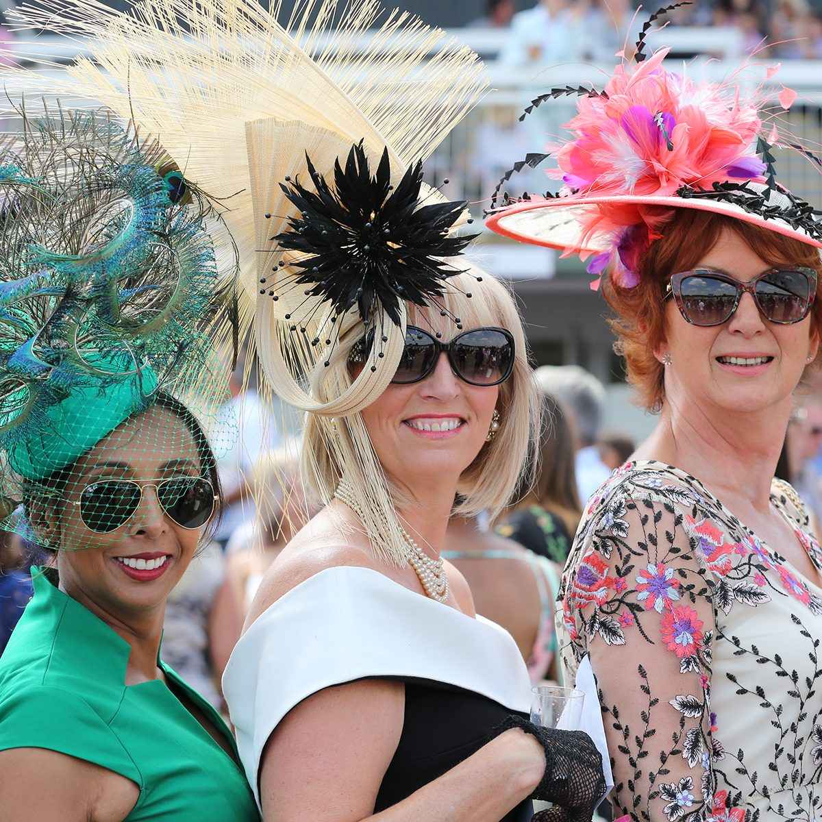 A group of fashionable well dressed women pose whilst enjoying the social atmosphere at Market Rasen Races Ladies Day