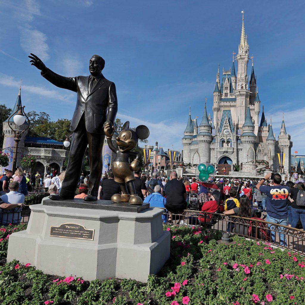 Mandatory Credit: Photo by John Raoux/AP/REX/Shutterstock (10180758b) Theme park guests walk near a statue of Walt Disney and Mickey Mouse in front of the Cinderella castle in the Magic Kingdom at Walt Disney World in Lake Buena Vista, Fla Disney World, Lake Buena Vista, USA - 09 Jan 2019