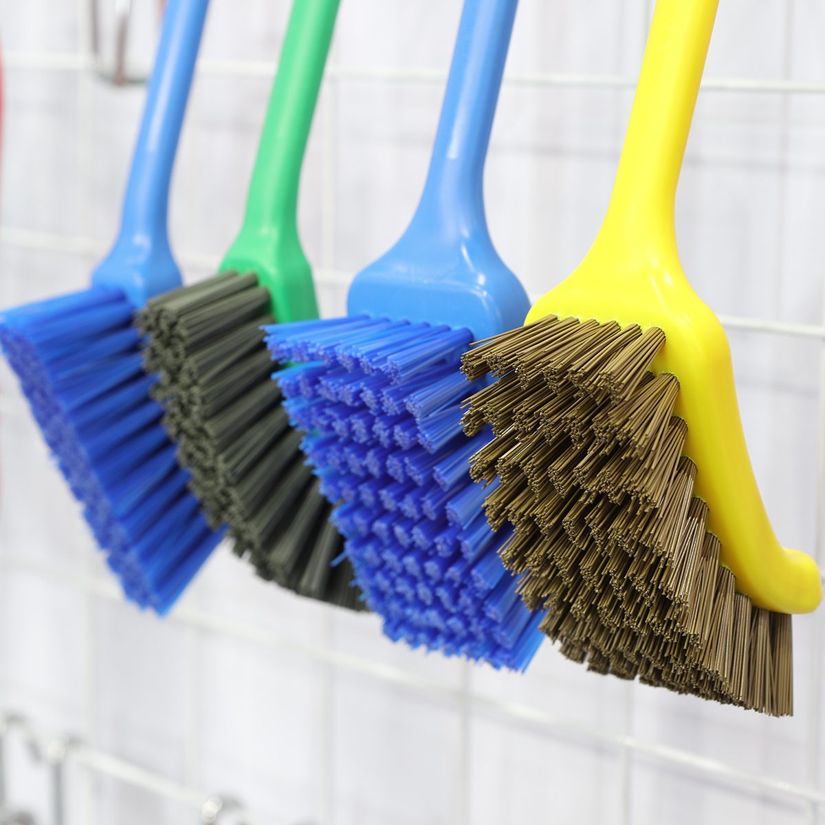 plastic cleaning brushes in supermarket hanger ; close up