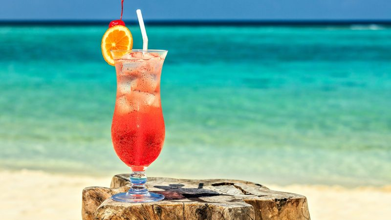 Glass of red drink is on the beach table