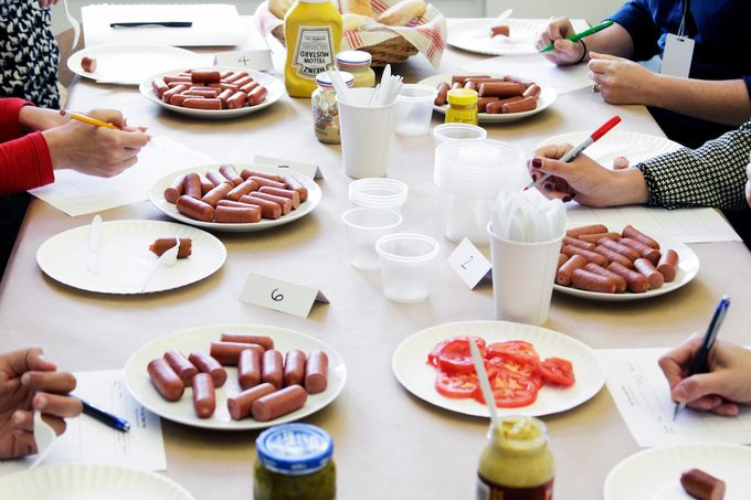Panel of testers sampling different brands to find the best hot dog.