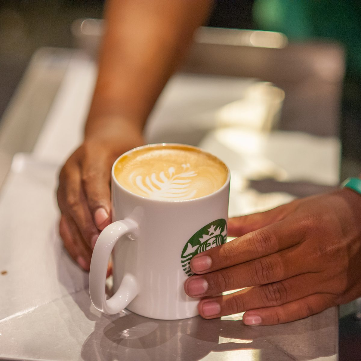 lose up of Starbucks Coffee Barista is hand over a coffee latte to the customers.
