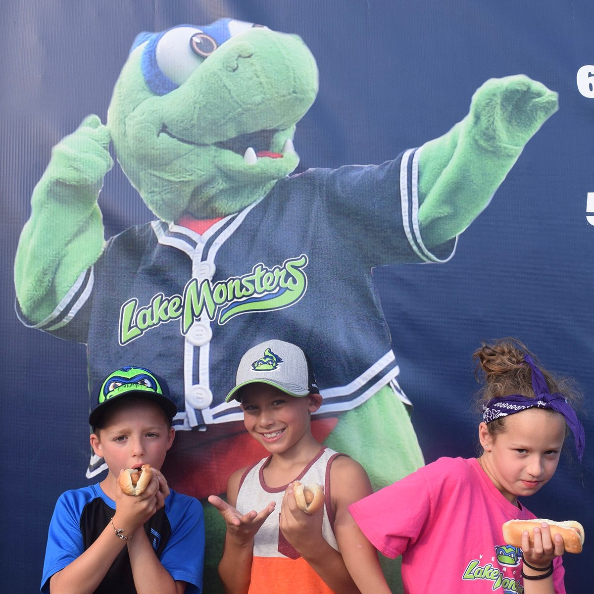 Three kids posing for picture in front of monster mascot
