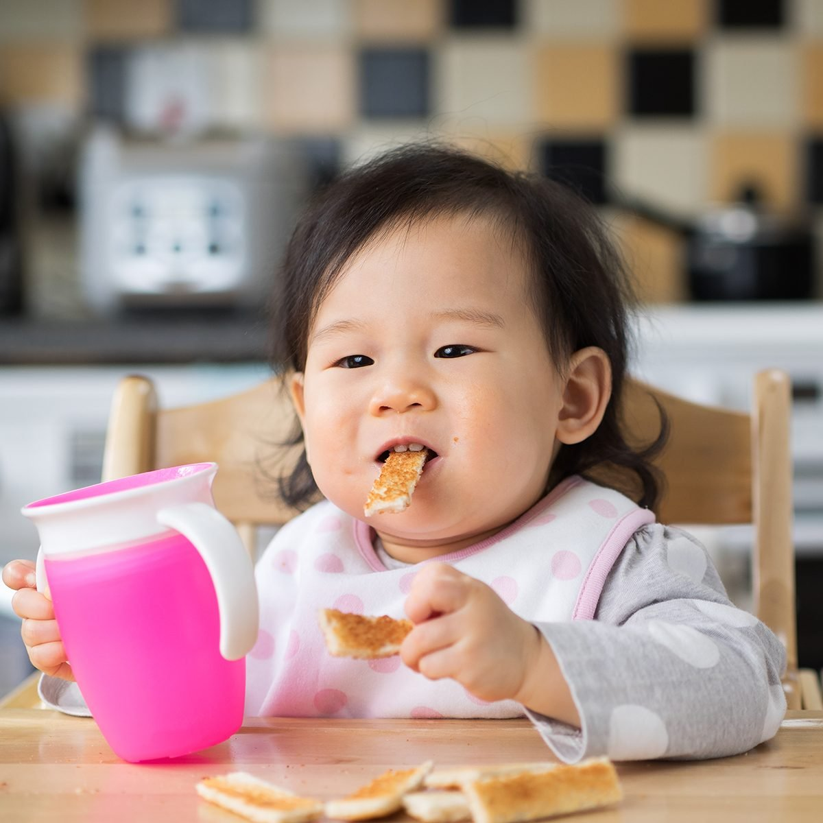 Asian baby girl eating toasted at home kitchen