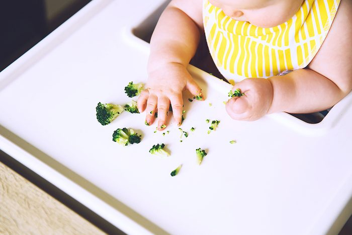 messy smiling baby eats with fingers broccoli in high chair