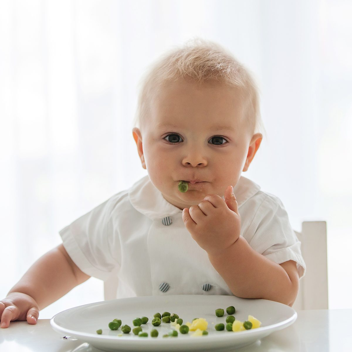 Toddler child, cute boy in white shirt, eating pea at home